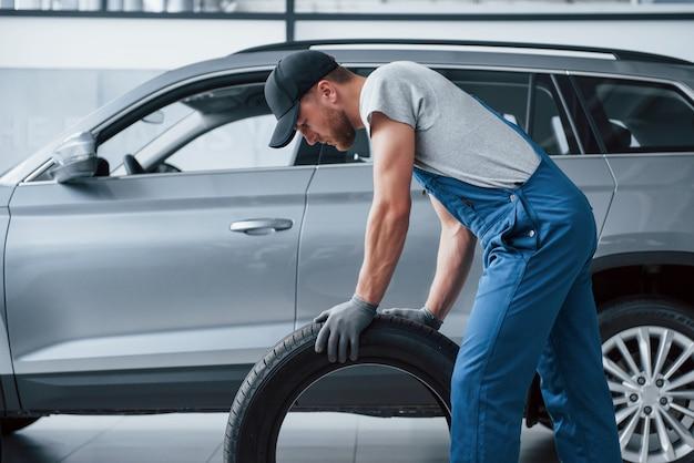 Este deve se encaixar perfeitamente. mecânico segurando um pneu na oficina. substituição de pneus de inverno e verão Foto gratuita