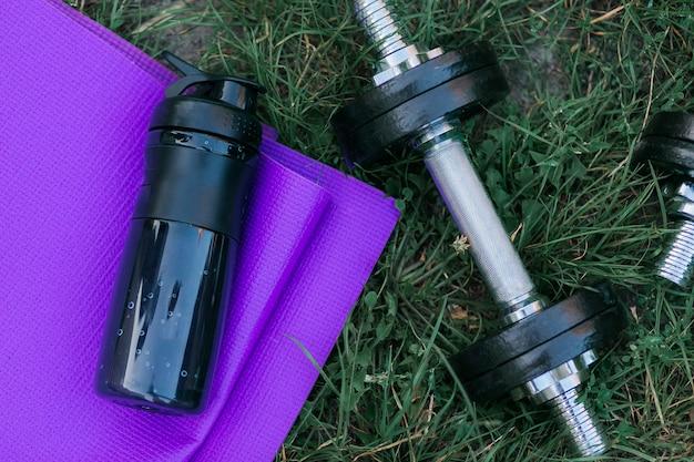 Esteira roxa da ioga, garrafa de água e dumbbell preto na grama verde. Foto gratuita