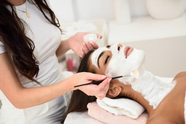 Estética, aplicando uma máscara para o rosto de uma mulher bonita Foto Premium
