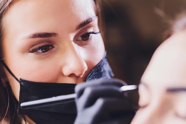 Esteticista aplica tinta de hena nas sobrancelhas aparadas em um salão de beleza Foto Premium