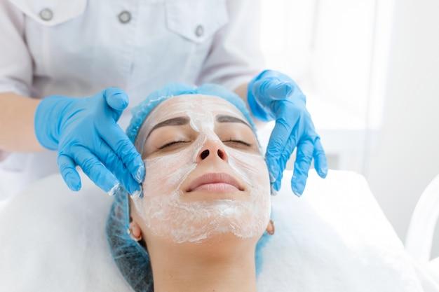 Esteticista aplica uma máscara no rosto de um paciente para cuidar da pele Foto Premium
