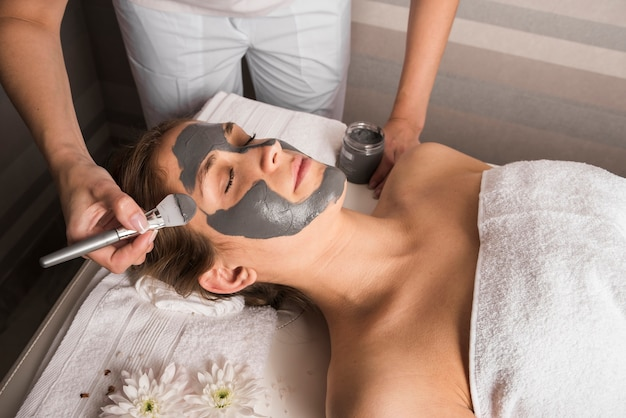 Esteticista, aplicando, máscara rosto, com, escova, ligado, mulher, rosto Foto gratuita