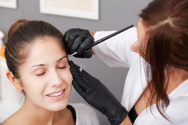 Esteticista aplicar maquiagem permanente nas sobrancelhas Foto Premium