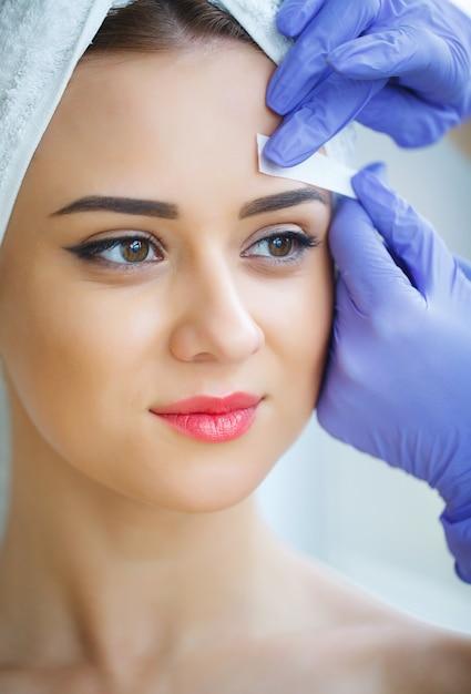 Esteticista depilação de sobrancelhas de mulher jovem no centro de spa Foto Premium