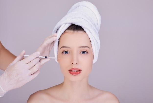 Esteticista faz injeção de rosto para uma jovem morena. Foto Premium