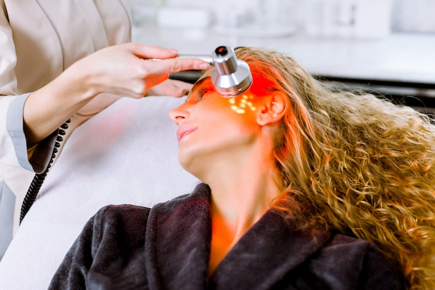 Esteticista fazendo terapia de luz led vermelha para mulher loira no salão de beleza, terapia de foto facial para limpeza dos poros da pele. tratamentos anti-envelhecimento e procedimento de rejuvenescimento da foto, close-up Foto Premium