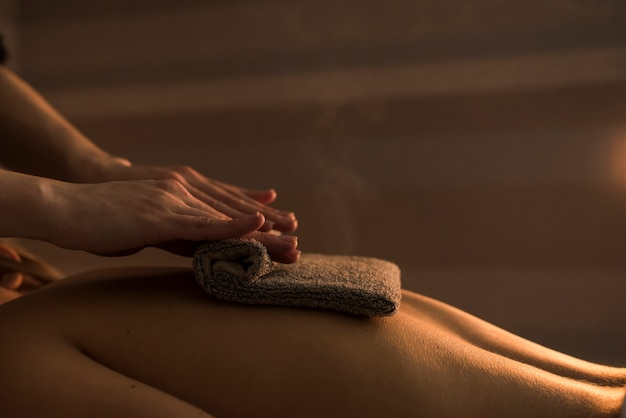 Esteticista, massaging, costas mulher, com, toalha quente Foto gratuita