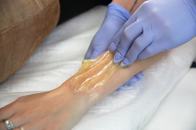 Esteticista remove o cabelo da mão de uma mulher. Foto Premium