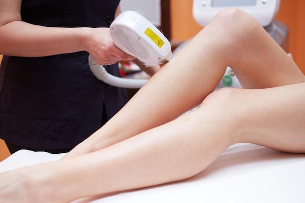 Esteticista, removendo o cabelo da jovem mulher com laser Foto Premium