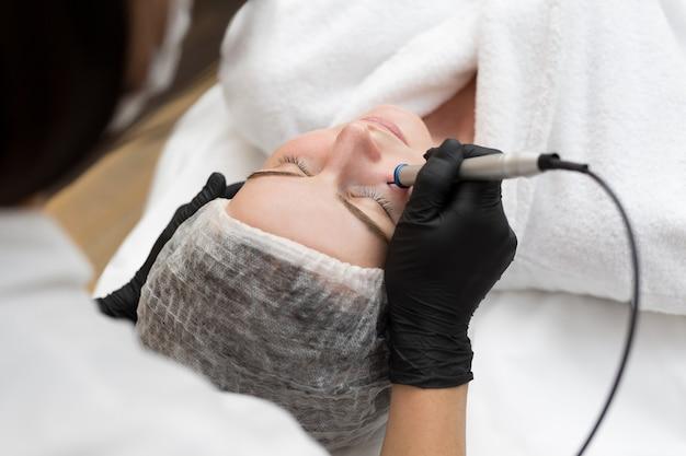 Esteticista terapeuta faz tratamento a laser no rosto de jovem em clínica de spa de beleza. Foto Premium
