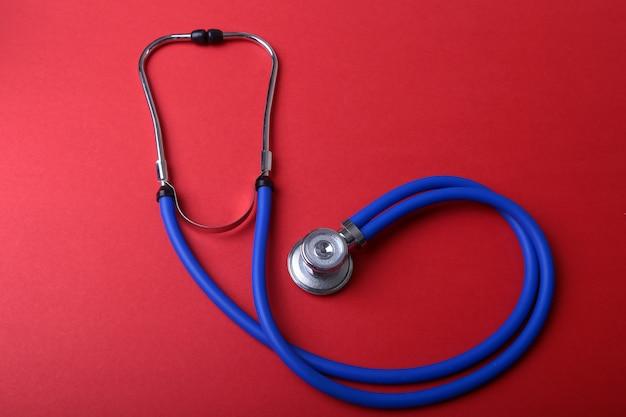 Estetoscópio azul médico isolado no vermelho Foto Premium