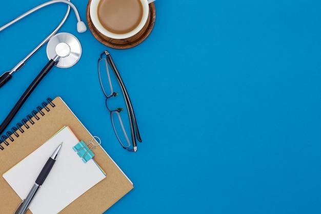 Estetoscópio com caderno, caneta, papel branco, xícara de café, copos, sobre fundo azul Foto Premium
