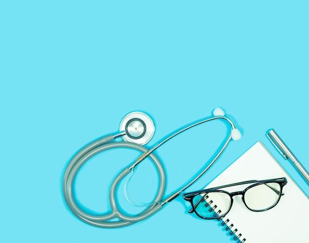 Estetoscópio com óculos no caderno em branco e caneta em fundo azul Foto Premium