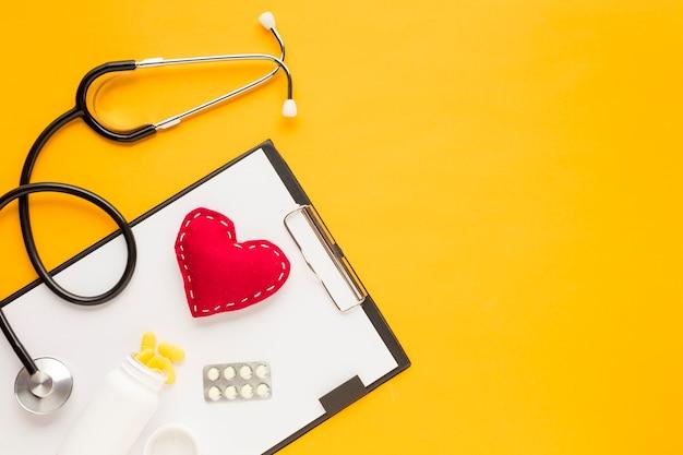 Estetoscópio; coração costurado; medicamento caindo de garrafas; blister embalado medicina com prancheta sobre a mesa amarela Foto gratuita