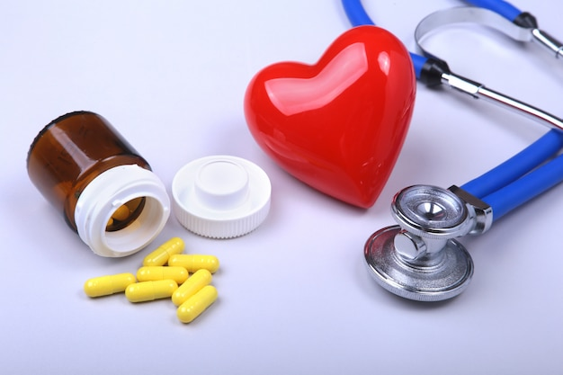 Estetoscópio, coração vermelho e pílulas sortidas. Foto Premium