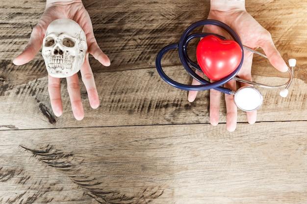 Estetoscópio e coração vermelho na mão esquerda, crânio na mão direita. escolhendo cuidados de saúde e morrer c Foto Premium
