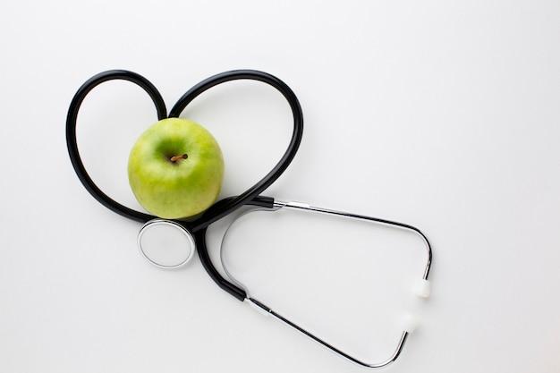 Estetoscópio e maçã verde plana leigos Foto gratuita