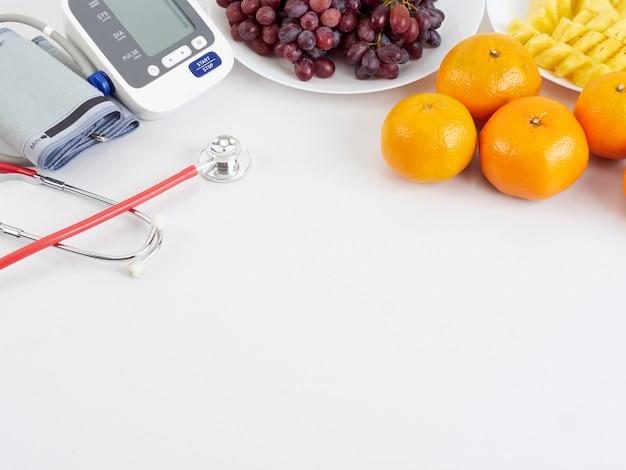 Estetoscópio e monitor automático de pressão arterial com frutas Foto Premium