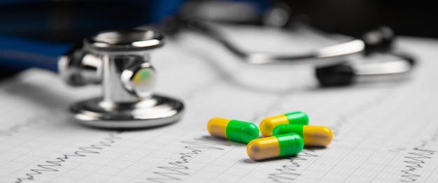Estetoscópio e pílulas coloridas deitado na folha com o eletrocardiograma Foto Premium
