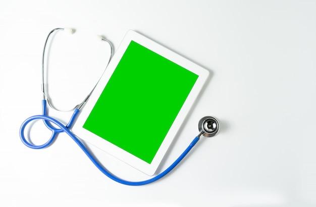 Estetoscópio e tablet na tela verde, fundo branco, cópia espaço para seu texto Foto Premium