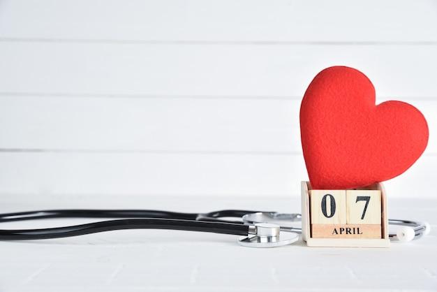 Estetoscópio e vermelho coração com calendário de bloco de madeira de 7 de abril de texto sobre fundo branco de madeira. Foto Premium
