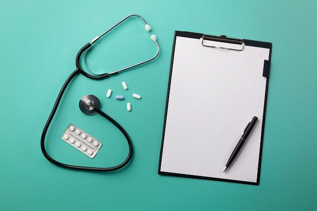 Estetoscópio, em, doutores, escrivaninha, com, tabuleta, caneta, e, pílulas Foto Premium