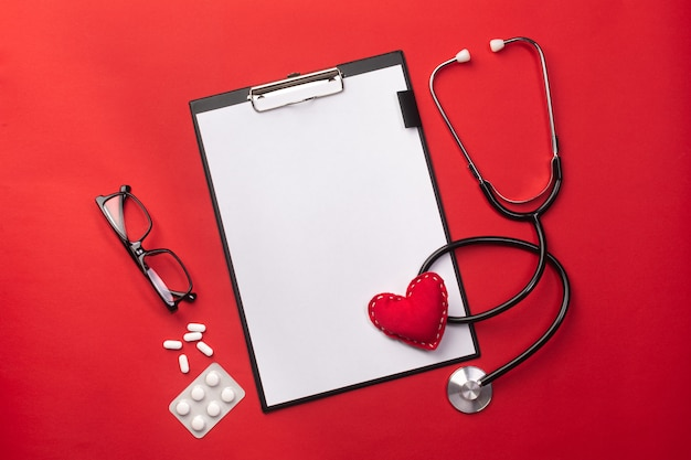 Estetoscópio, em, doutores, escrivaninha, com, tabuleta, coração, e, pílulas Foto Premium