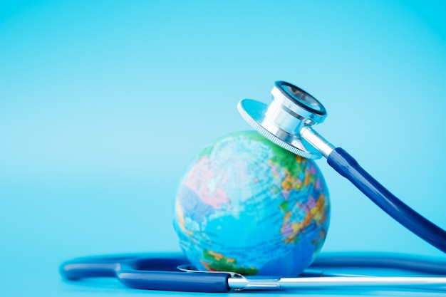 Estetoscópio enrolado ao redor do globo em fundos azuis. Foto Premium