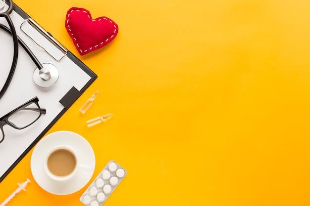 Estetoscópio; forma de coração costurada; xícara de café; medicamento embalado em blister; injeção sobre o pano de fundo amarelo Foto gratuita