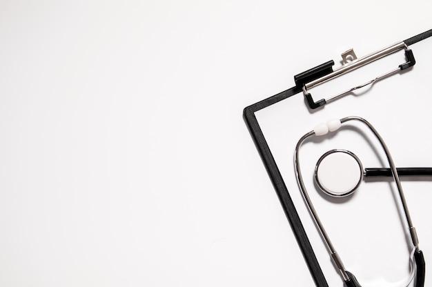 Estetoscópio médico ou phonendoscope isolado no fundo branco recortado. estetoscópio e prancheta com folha de papel em branco e espaço para cópia. conceito médico Foto gratuita