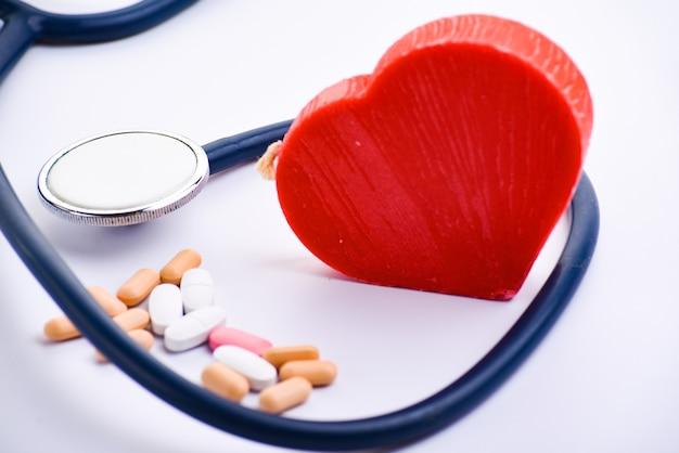 Estetoscópio médico, pílulas e coração vermelho. conceito de cardiologia Foto Premium
