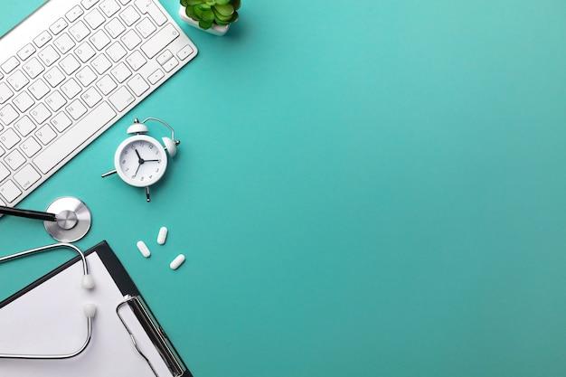 Estetoscópio na mesa de médicos com caderno, caneta, teclado, despertador e pílulas Foto Premium