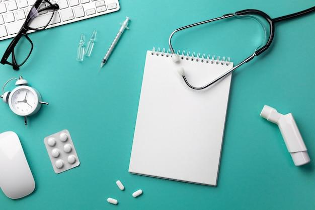 Estetoscópio na mesa de médicos com teclado, despertador, óculos, inalador, seringa, ampolas, inalador e pílulas Foto Premium