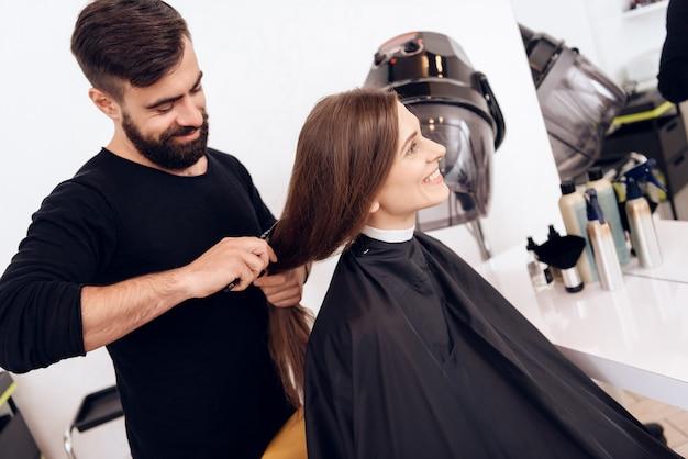 Estilista de cabeleireiro é pentear jovem com cabelo castanho Foto Premium