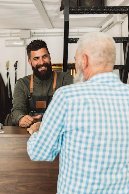 Estilista de cabelo barbudo sorridente conversando com o cliente idoso no salão Foto gratuita
