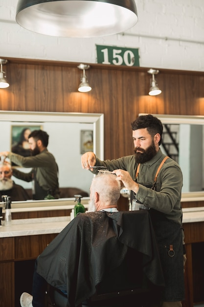 Estilista de cabelo fazendo o corte de cabelo para o cliente na barbearia Foto gratuita