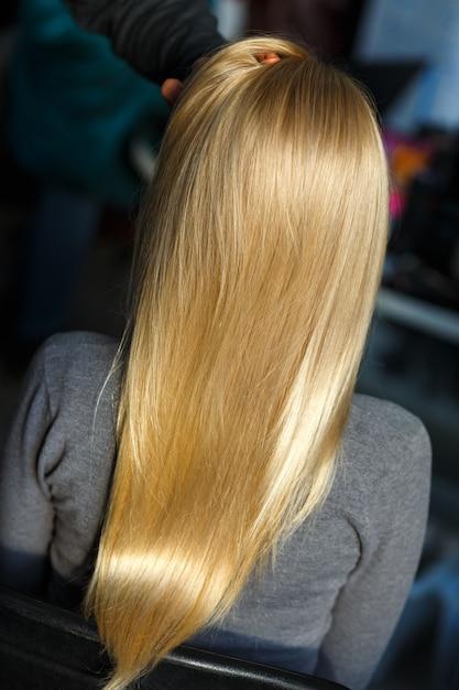 Estilista demonstrar cabelo loiro feminino Foto Premium