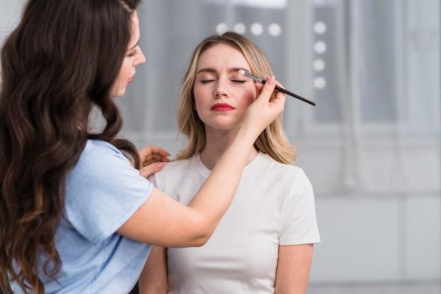 Estilista fazendo maquiagem de sombra para mulher loira Foto gratuita