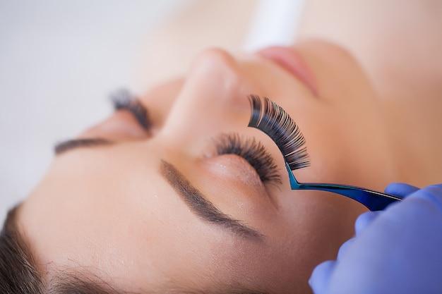 Estilista profissional alongamento cílios femininos. Foto Premium