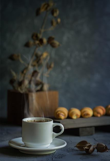 Estilo antigo ainda vida com croissants e uma xícara de café quente Foto Premium