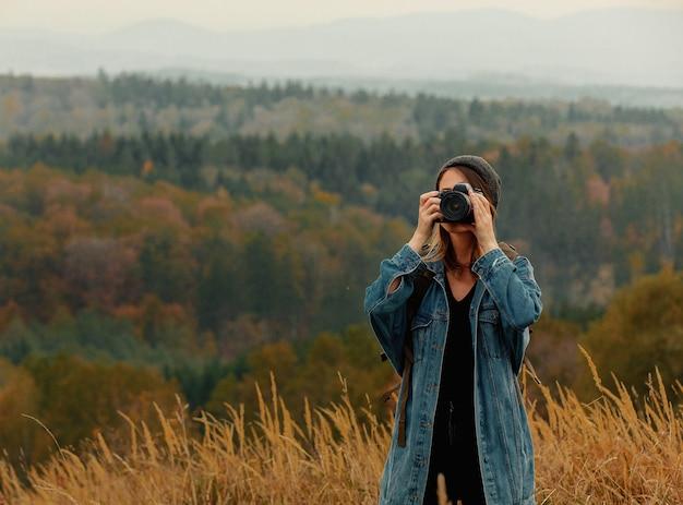 Estilo de mulher com câmera fotográfica e mochila na zona rural com montanhas Foto Premium