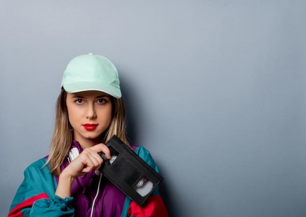 Estilo de mulher no estilo de roupa dos anos 90 com cassete de vídeo vhs Foto Premium