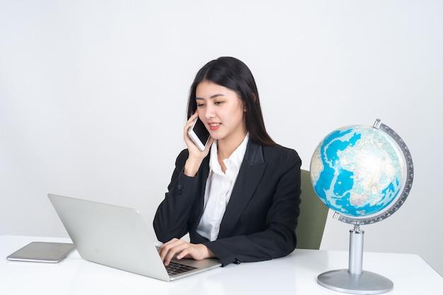 Estilo de vida bonito jovem mulher de negócios asiáticos usando computador portátil e telefone inteligente na mesa de escritório Foto gratuita