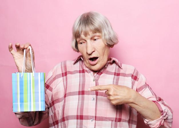 Estilo de vida e conceito de pessoas de mulher feliz sênior com sacola de compras sobre rosa Foto Premium