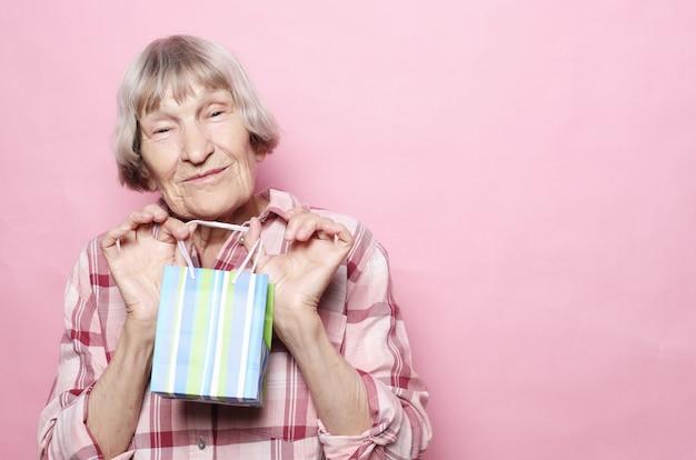 Estilo de vida e conceito de pessoas: feliz mulher sênior com sacola de compras sobre fundo rosa Foto Premium
