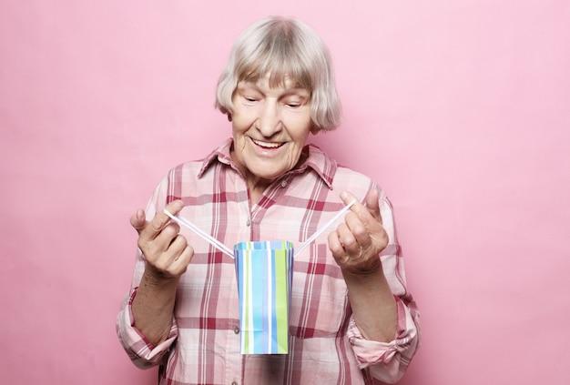 Estilo de vida e conceito de pessoas: feliz mulher sênior com sacola de compras Foto Premium