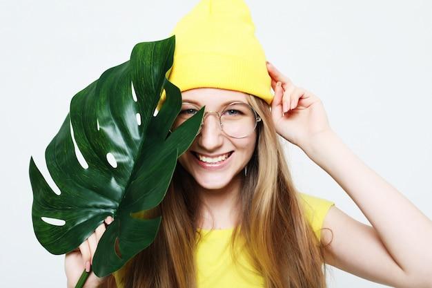 Estilo de vida, emoção e conceito de pessoas: mulher sorridente por trás da folha grande Foto Premium