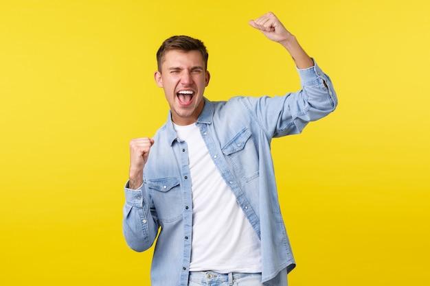 Estilo de vida, emoções das pessoas e conceito de lazer de verão. homem feliz bonito entusiasmado levantando as mãos, cantando e gritando sim como vencedor, triunfando sobre o prêmio da loteria, fundo amarelo. Foto gratuita