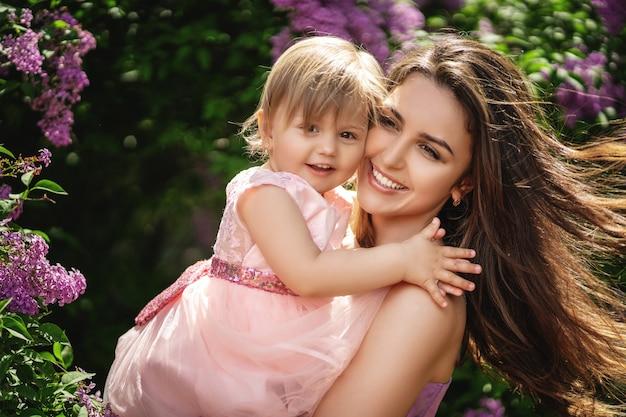 Estilo de vida retrato mãe e filha em felicidade do lado de fora nas árvores florescendo Foto Premium