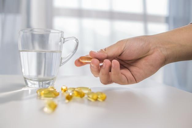 Estilo de vida saudável, medicamentos, suplementos nutricionais e conceito de pessoas - close up de mãos do sexo masculino segurando pílulas com cápsulas de óleo de fígado de bacalhau e copo de água Foto gratuita